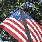 American flag with black mourning ribbon